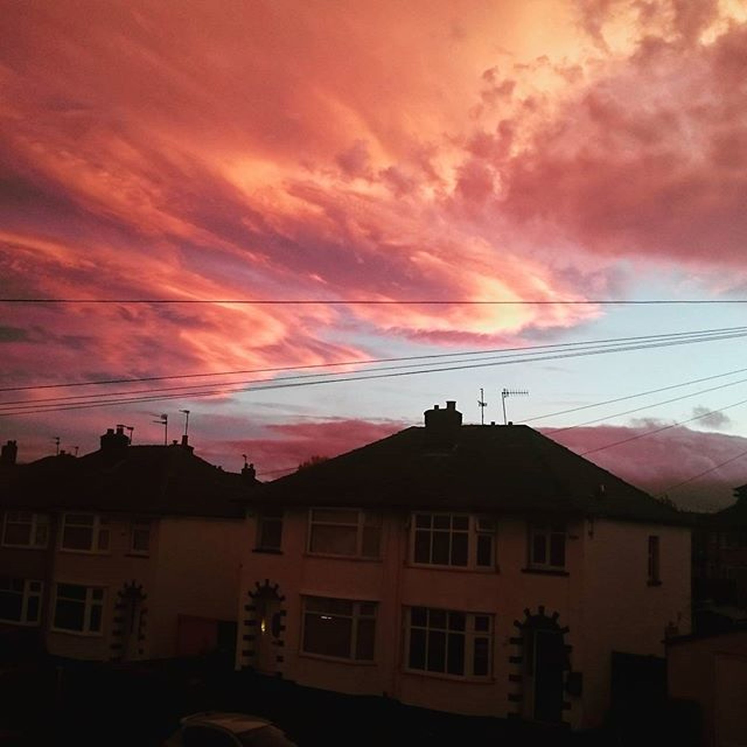 sunset, building exterior, architecture, sky, built structure, cloud - sky, orange color, house, cloudy, residential structure, cloud, power line, residential building, low angle view, silhouette, weather, dramatic sky, building, beauty in nature, nature