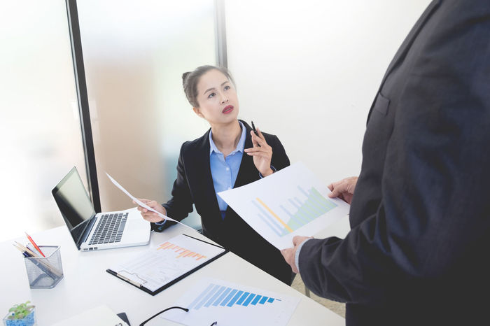 Business Businesswoman Communication Corporate Business Day Desk Finance Graph Holding Indoors  Laptop Occupation Office Paperwork Real People Talking Technology Two People Using Laptop Well-dressed Wireless Technology Women Working Young Adult Young Women