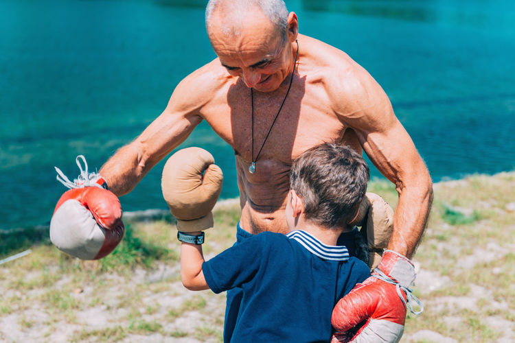 Shirtless Grandfather With Grandson Boxing By Swimming Pool