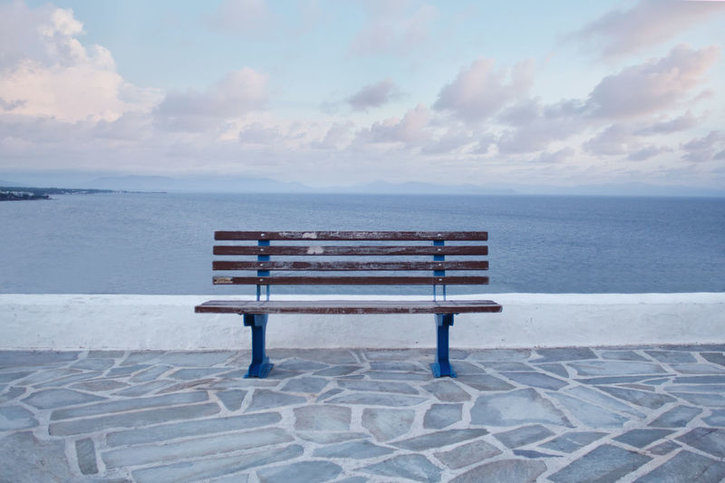 Empty bench on beach by sea against sky