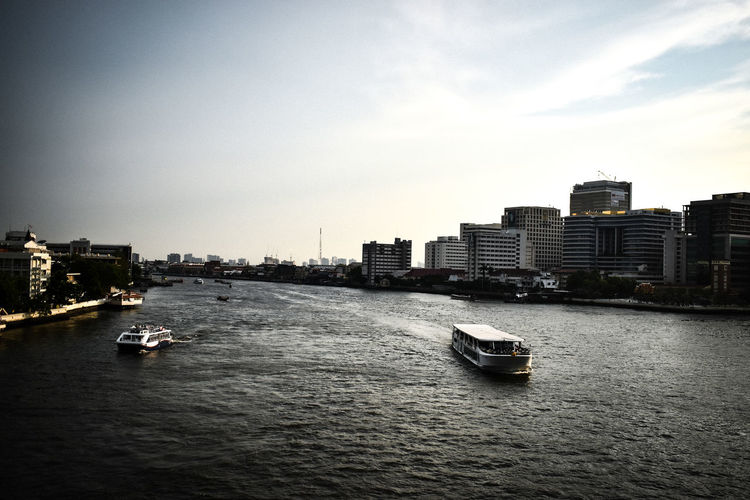 Boats in river by buildings in city against sky