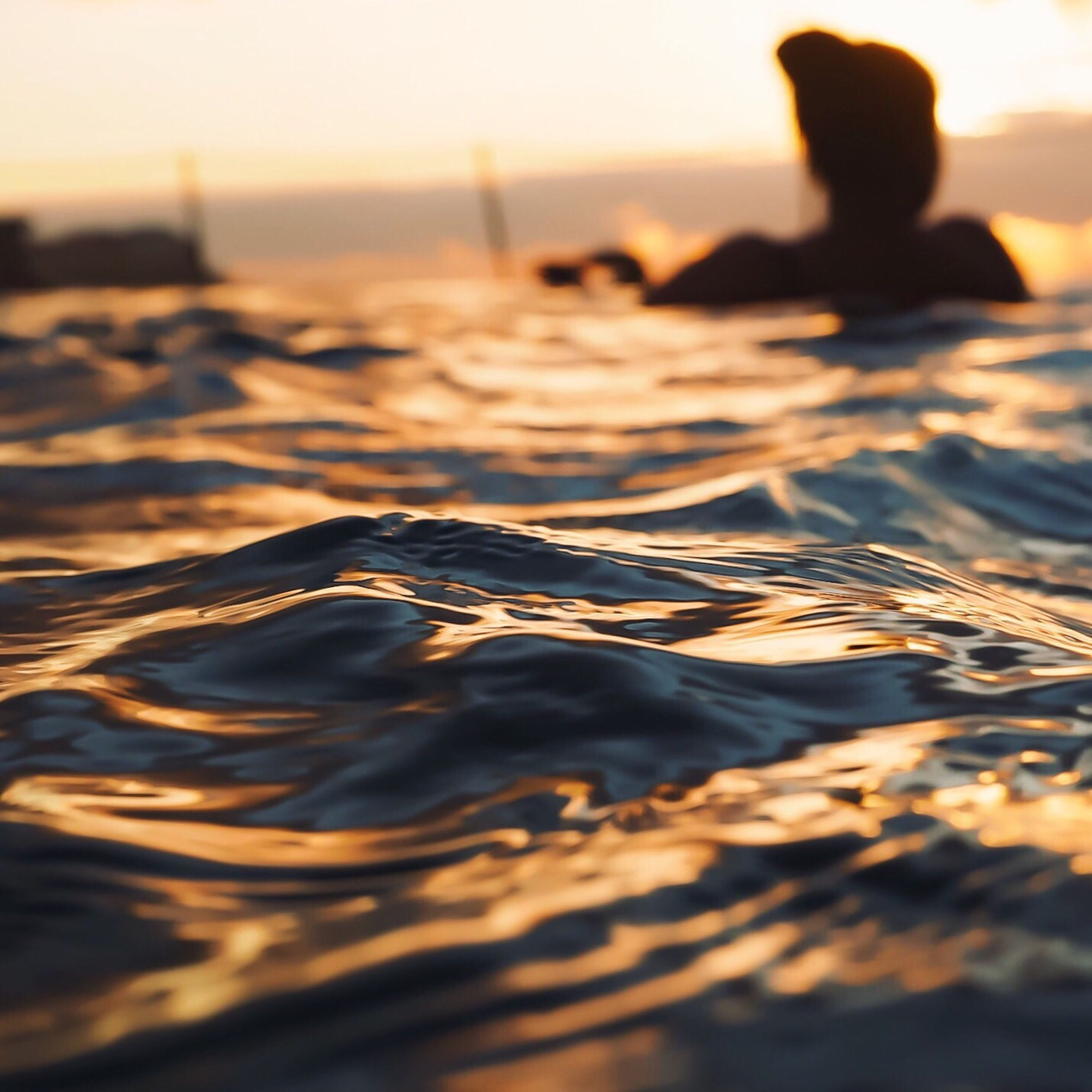 sea, water, waterfront, sunset, rippled, surface level, horizon over water, tranquil scene, tranquility, calm, selective focus, scenics, beauty in nature, nature, sky, outdoors, majestic, sun, shore, ocean, remote, outline