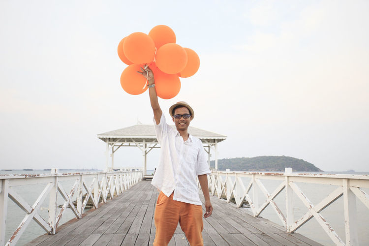 Portrait of man holding balloons while standing on pier against sky
