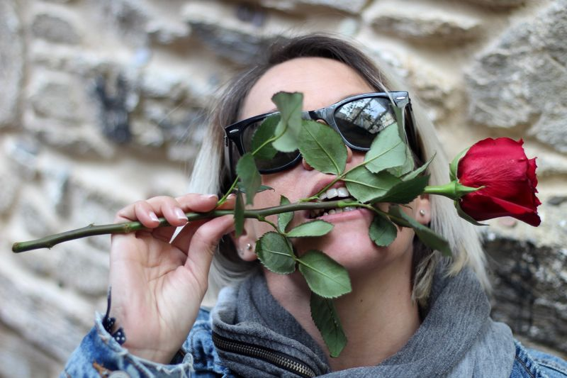 Mid adult woman biting rose outdoors