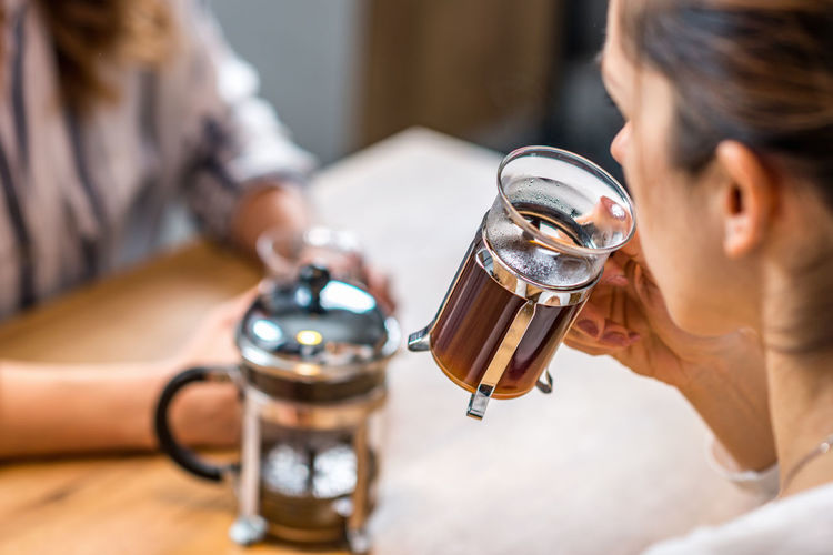 Girlfriends Having Coffee Together Coffee French Press Females Women Cafe Home Drink Young Girl Cup Hot Glass Two People Enjoy People Caucasian Happy Lifestyle Concept Caffeine Indoors  Holding Beautiful Adult Casual Enjoyment Break Table Aroma Woman Close Up Drinking Happiness Indoors  Togetherness
