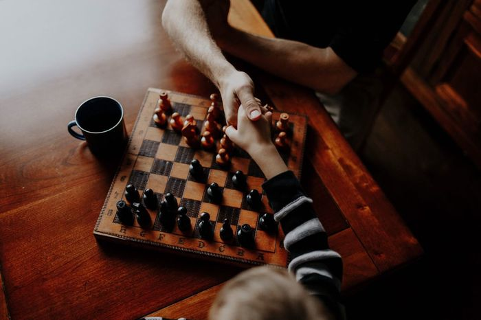 High angle view of people holding hands over chess board on table