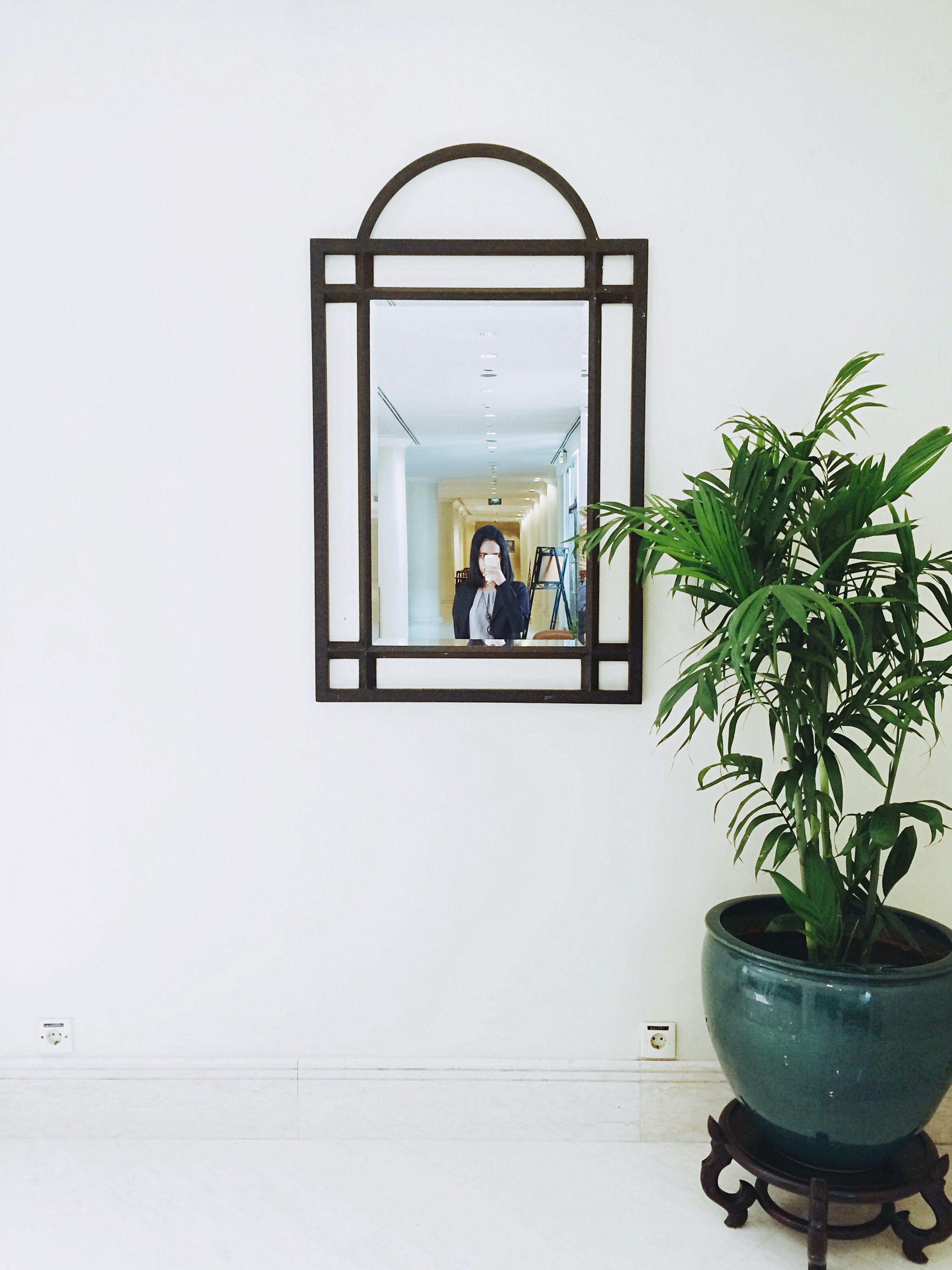 indoors, architecture, low angle view, built structure, glass - material, window, clear sky, lighting equipment, potted plant, mirror, day, wall - building feature, transparent, technology, copy space, men, hanging, reflection, full length