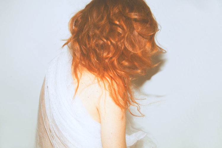 Rear view of woman with redhead wrapped in fabric against white background