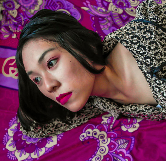 Portrait of beautiful woman lying on bed