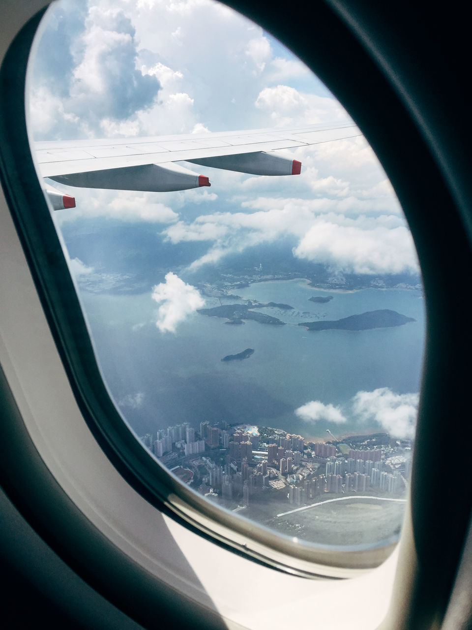 airplane, transportation, vehicle interior, sky, air vehicle, window, mode of transport, journey, travel, day, airplane wing, mid-air, cloud - sky, aerial view, flying, no people, vehicle part, cityscape, scenics, sea, landscape, nature, mountain, city, runway, close-up, outdoors