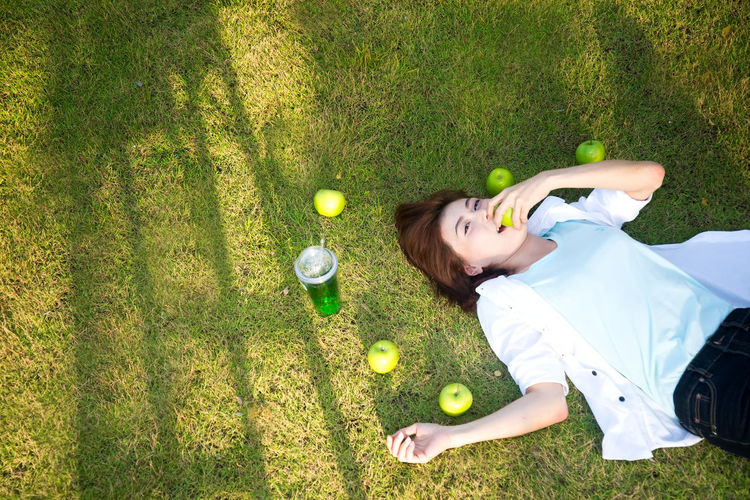 High angle portrait of woman eating apple while lying on grass