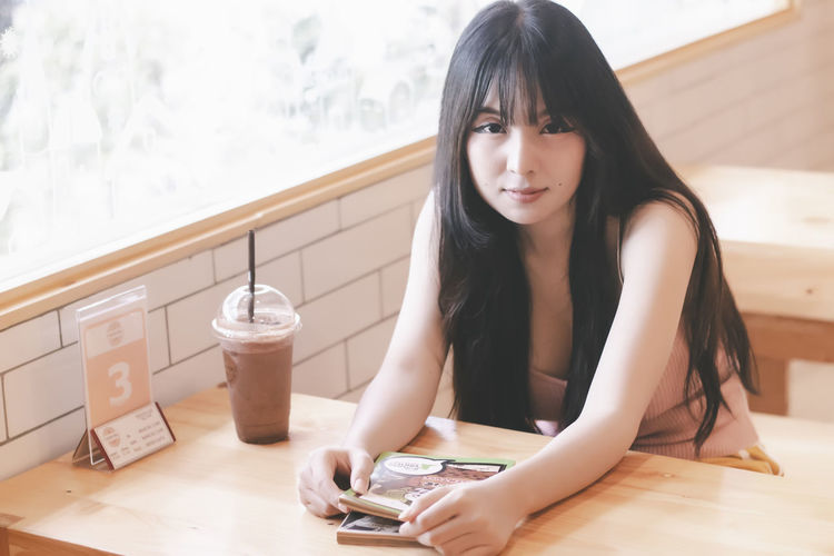 Portrait of young woman using smart phone on table
