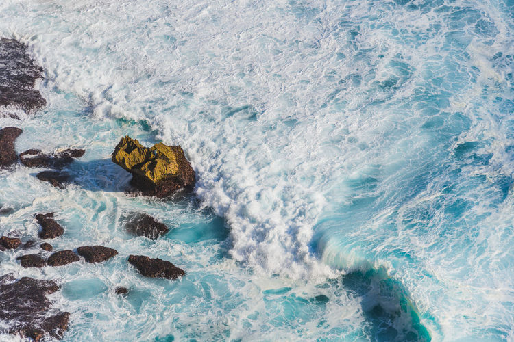 High Angle View Of Wave Splashing At Rocky Shore
