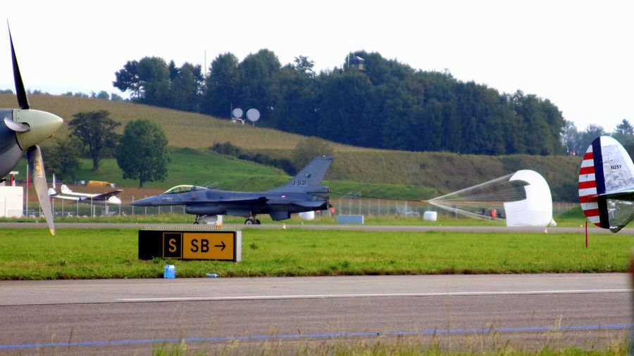 General Dynamics F-16AM Fighting Falcon, Royal Netherlands AF, J-631 Taxiing after flight display with drag chute deployed. Air14 Fighting Falcon Netherlands RNAF Air Vehicle Airplane Airport Airport Runway Day Grass No People Outdoors Payerne Runway Sky Transportation Tree