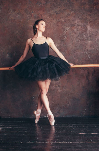 Ballet dancer ballerina in beautiful black dress tutu skirt posing in loft studio Full Length Dancing One Person Women Ballet Dancer Portrait Fashion Ballet Looking At Camera Young Adult Indoors  Real People Beauty Young Women Beautiful Woman Wall - Building Feature Front View Dress Skill  Tiptoe Teenager