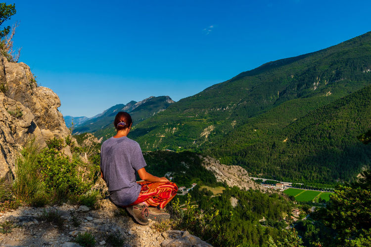 Rear view of woman sitting on rock against mountain