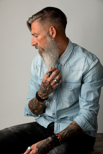 Bearded Man Sitting Against Wall