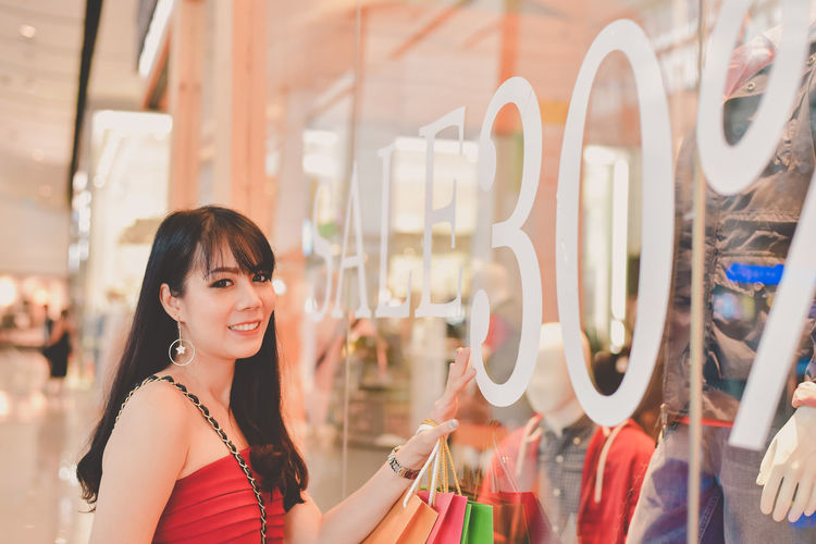 Young Woman Entering In Clothing Store At Mall