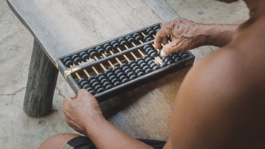 Midsection of shirtless man playing with abacus