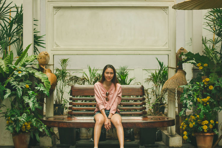 Portrait of woman sitting on chair against plants