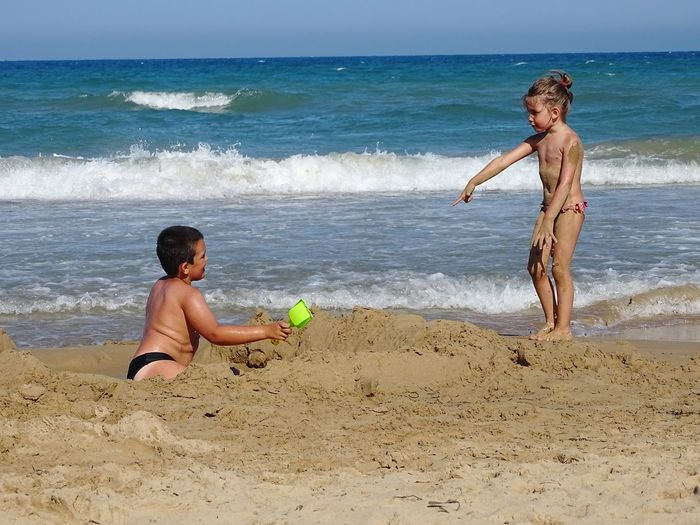 Shirtless Siblings Playing With Sand At Beach