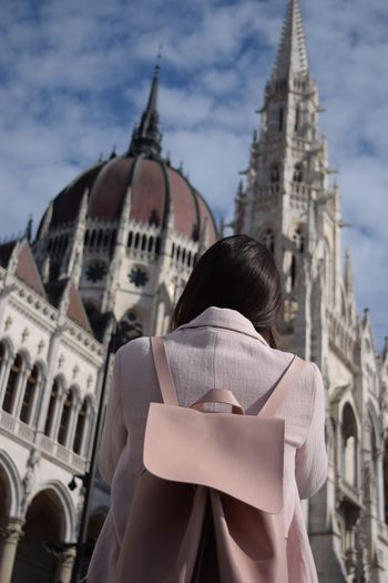 Rear View Of Woman Against Hungarian Parliament Building