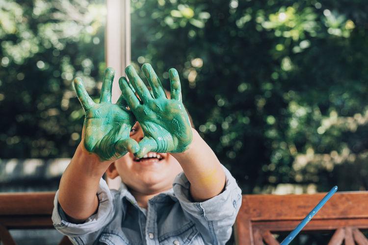 Smilig boy showing messy hands over face