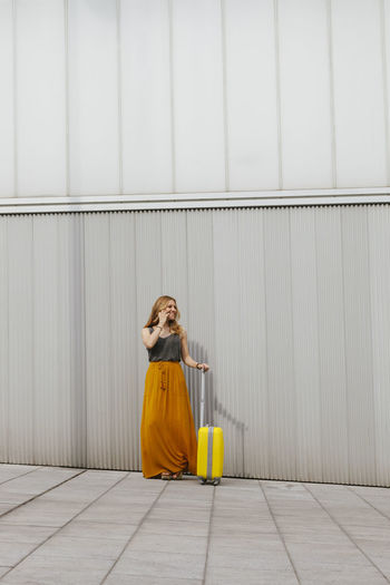 Woman sitting against yellow wall