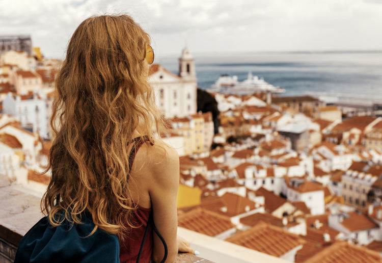 Rear view of woman standing over buildings against sea and sky