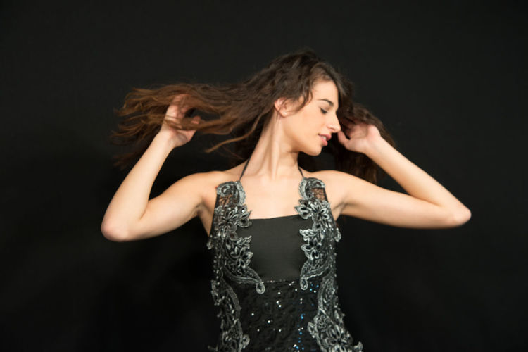 Fashionable teenage girl tossing hair while standing against black background
