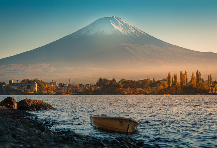 Scenic view of lake and snowcapped mt fuji against clear sky during sunset