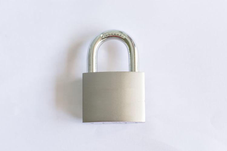 Close-up of padlocks on metal against white background