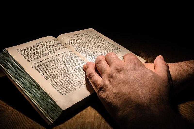 Close-up of hands holding bible in darkroom