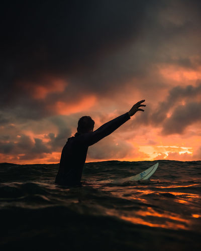 Silhouette man surfing on sea against cloudy sky during sunset