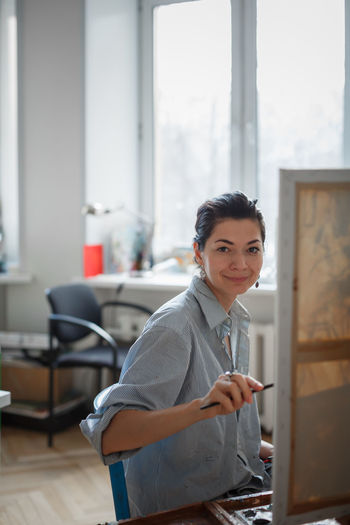 Portrait Of Woman Painting On Canvas While Sitting At Home