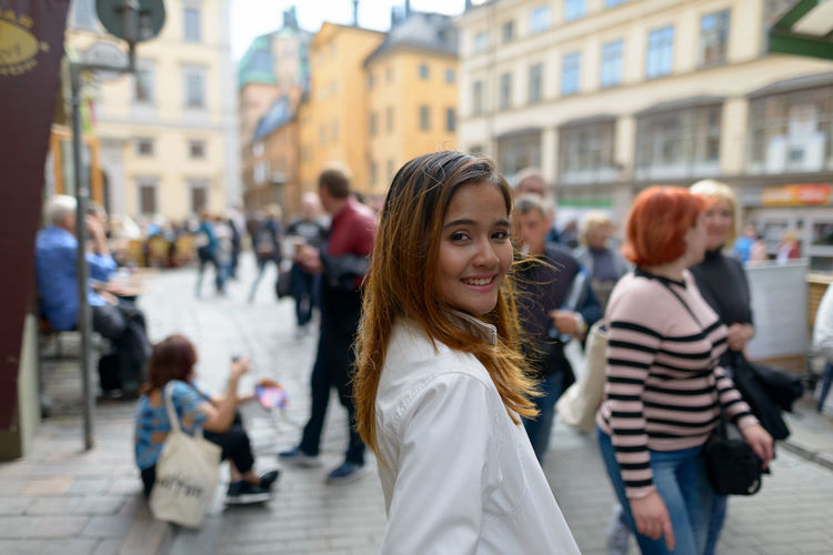 Portrait of woman standing on busy street in city