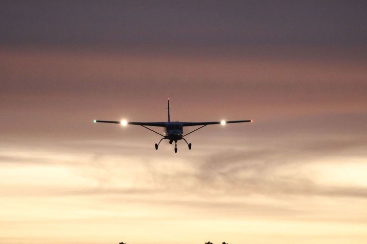 Low Angle View Of Airplane Against Sky At Sunset