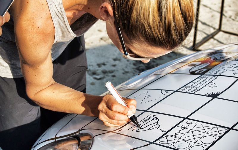 Woman Drawing On Car Hood