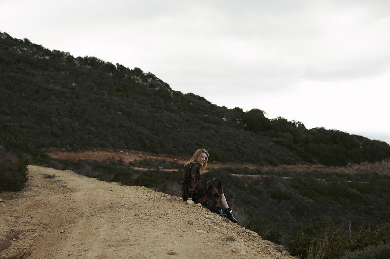 Teenage Girl Sitting On Mountain Against Sky