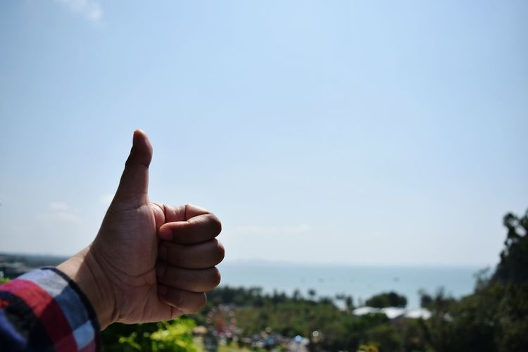 Close-up of hand showing thumbs up against clear sky