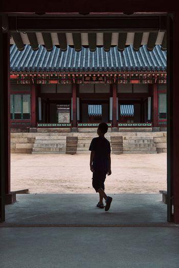 Full length rear view of boy walking in temple