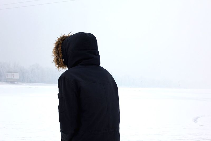 Rear View Of Man Standing In Snow Against Sky