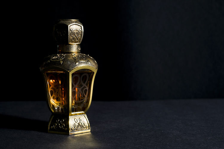 Exclusive Arab perfume in bottle, isolated in black background. Ancient Beautiful Black Background Classic Darkness Dim Light Exclusive  Sweet Smell Bottle Cap Copy Space. Cosmetics Fragrance Fragrant Isolated On Black Light And Shadow Nice Perfume Retro Style Single Object Studio Shot