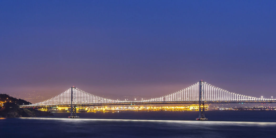 Suspension bridge over river against blue sky