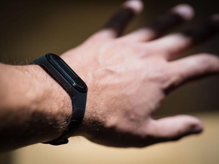 Close-up of human hand and fitness band against blurred background