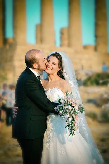 Bridegroom Kissing Happy Bride On Cheek During Sunset