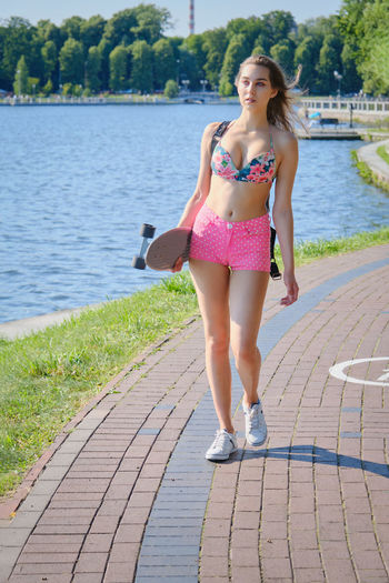 Portrait of a beautiful young woman on footpath by lake