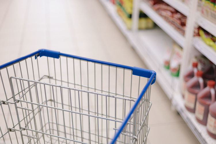 Concept image of buying. Shopping trolley in a Tesco Hypermarket with blurry background of groceries on the rack. Focused only at the trolley. Tesco  Supermarket Hypermarket Shopping Shopping Cart Shopping Mall Trolley Store Retail  Consumerism No People Indoors  Empty Close-up Market Focus On Foreground Groceries Absence Buying Selective Focus Shelf In A Row Steel Aisle