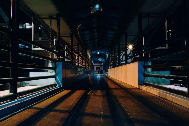 Double exposure of man standing on bridge at night