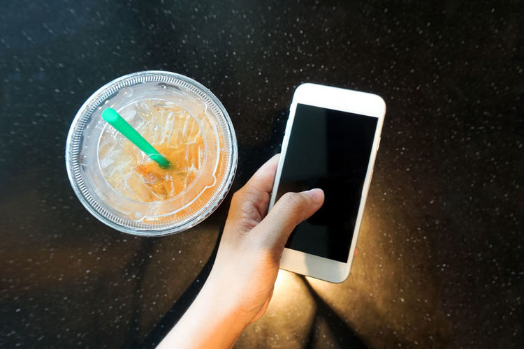Close-Up Of Hand Holding Smart Phone On Table